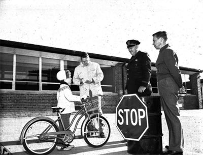 child on bike with police officers