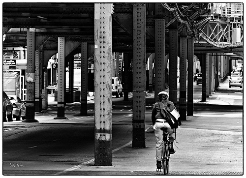 Bicyclist with elevated train pylons in Chicago